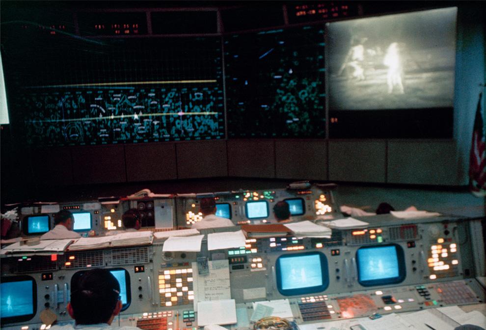 31) Вид на диспетчерскую миссии в центре управления полетов, здание 30. На экране видно Нила Армстронга и База Олдрина на поверхности Луны. (NASA)